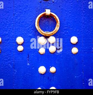 rostiges Metall Nagel schmutzig abgespeckte Farbe in den blauen Holz Tür und Marokko Klopfer - Stockfoto