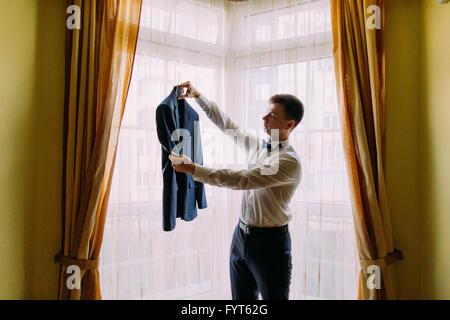 Junger Mann in weißem Hemd und Fliege hält Business Jacke Mantel - Stockfoto
