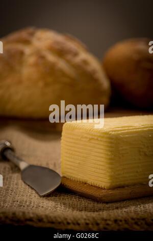 Hand aufgewühlt selbst gemachter Butter auf hölzernen Paddel mit Buttermesser und Brot. - Stockfoto