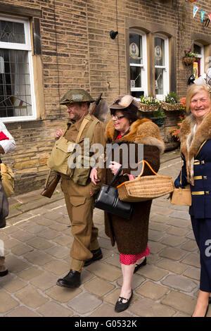 Großbritannien, England, Yorkshire, Haworth 40er Jahre Wochenende, Main Street, paar in Kriegszeiten Kostüm zu Fuß - Stockfoto