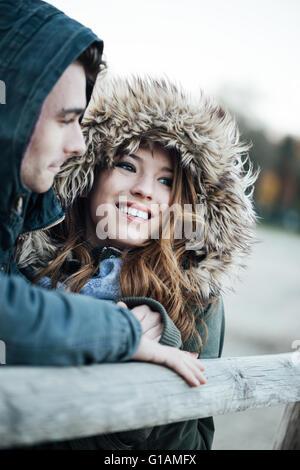 Lächelnd Liebespaar mit Hauben Datierung während einer kalten Winter Tag, Liebe und Beziehungen-Konzepts - Stockfoto