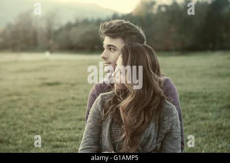 Junge Teenager im Freien, auf dem Rasen sitzen und kuscheln, umarmt er seine Freundin, Beziehungen und Gefühle Konzept - Stockfoto