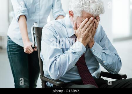 Traurig deprimiert Mann im Rollstuhl mit Kopf in Händen, eine Frau ihn kümmert sich - Stockfoto