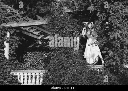 Junge Frau im viktorianischen Kleid steht auf dem Geländer auf der Terrasse, umgeben von Kletterpflanzen - Stockfoto