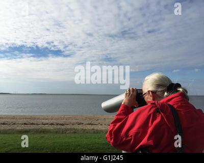 Senior-Frau am Strand mit Blick durch ein Fernglas, Esbjerg, Dänemark - Stockfoto