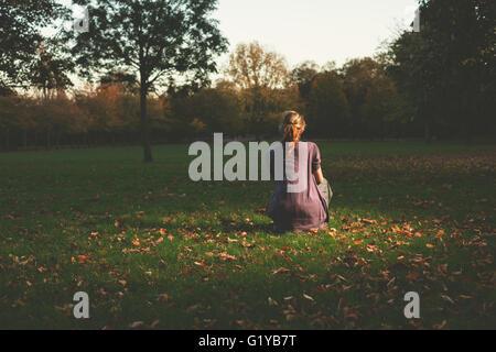 Eine junge Frau ist auf dem Rasen im Park am Abend Standortwahl. - Stockfoto