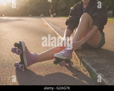 Eine junge Frau sitzt auf dem Boden und setzt auf Rollschuhen im Park bei Sonnenuntergang - Stockfoto