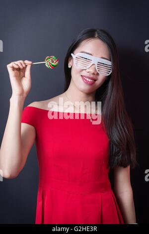 Schöne Frau mit einen Lolli beim Tragen von roten Kleid - Stockfoto