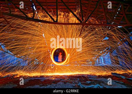 Brennenden Stahl Wolle spinnen. Duschen der glühenden Funken vom Spinnen Stahlwolle in Schutt und Asche - Stockfoto
