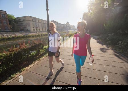 zwei Freundinnen der mittleren Alters, die Joggen haben Morgengymnastik mit Sonnenaufgang im Hintergrund - Stockfoto
