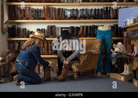 Shop Assistant hilft Kunden mit Stiefeln - Stockfoto