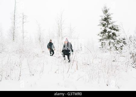 Finnland, Jyväskylä, Saakoski, junges Paar Wandern zwischen kahlen Bäumen im winter - Stockfoto