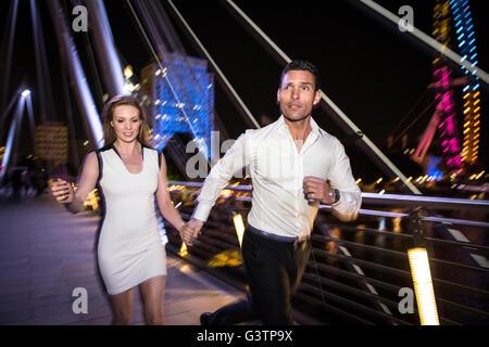 Eine elegant gekleidete paar laufen über die Millennium Bridge in London in der Nacht. - Stockfoto