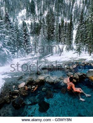 Wald im Winter, Mann sitzt in einer heißen Quelle. - Stockfoto