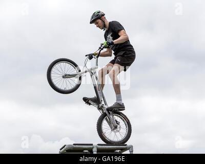 Stunt-Fahrer mit seinem Stunt Bike auf dem Hinterrad auf einer hohen Plattform - Stockfoto
