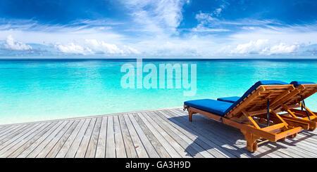 Liegestühle am Steg vor tropischen Insel - Stockfoto