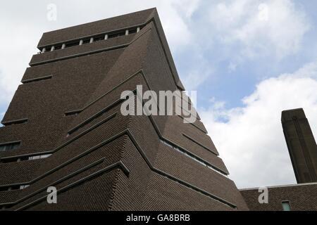 Der Schornstein von der Tate Modern Power House blickt auf die neuen Flügel. - Stockfoto