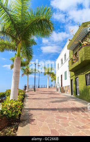Palmen an der Promenade in der Stadt Alcala mit typisch kanarischer Architektur auf der Küste von Teneriffa, Kanarische - Stockfoto