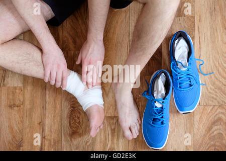 massieren den verletzten Knöchel nach einem Unfall Sport Sportler - Stockfoto