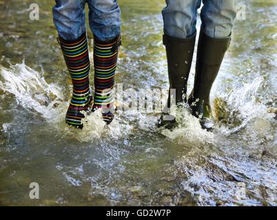 Glückliches Paar tragen bunte Regen Stiefel. Freude und Spaß-Konzept - Stockfoto
