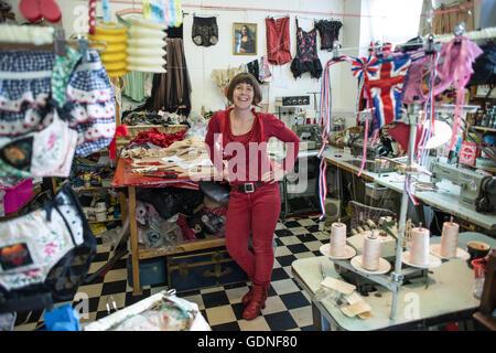 Eine Frau in roter Bluse, Hose und Halsketten lächelnd und steht in der Mitte eine Schneiderei. - Stockfoto
