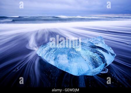 Wellen Waschen um einen kleinen Eisberg am Strand am Jökulsárlón in Island. - Stockfoto