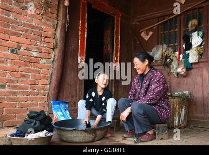 (160803) – XUNDIAN, 3. August 2016 (Xinhua)--10-Year-Old er Yuanxi hilft ihrer Großmutter in Fengle Dorf Yangjie - Stockfoto