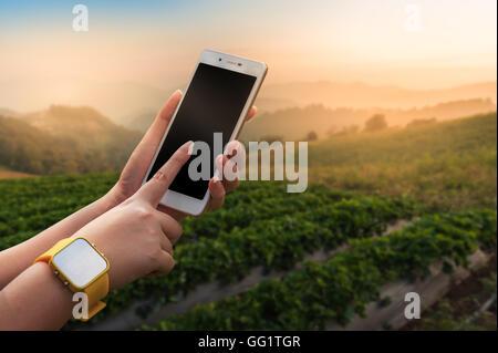 Junge Frau trägt gelbe Uhr morgen rechtzeitig auf Smartphone-Bildschirm mit verschwommenen Natur Hintergrund berühren - Stockfoto