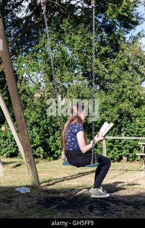 Gefährten, Entspannung, Mädchen, Mädchen lesen im Dorf Park, Kind, Park, schwarz, Wiese, Bäume, Freunde, Beziehung, - Stockfoto