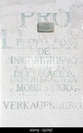 Gedruckte unlegible Wörter in verschiedenen Sprachen auf weißem Putz Wand am 5. August in Port Andratx, Mallorca, - Stockfoto