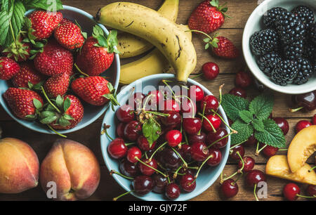 Sommer frische Früchte und Beeren-Vielfalt über hölzerne Kulisse, Draufsicht, horizontale Komposition - Stockfoto