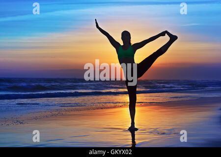 Schwarze Silhouette Frau stretching am Yoga Retreat am Sonnenuntergang Strand Sand, bunte Himmel, Ozean-Surf-Hintergrund. - Stockfoto