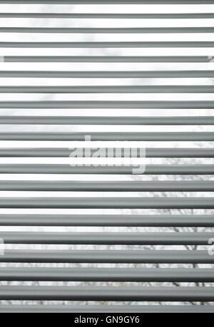 Bäume, die durch halb geschlossenen metallischen Jalousien gesehen - Stockfoto