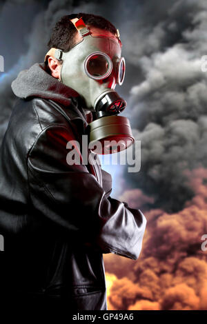Bewaffneter Mann mit Gasmaske über Explosion Hintergrund - Stockfoto