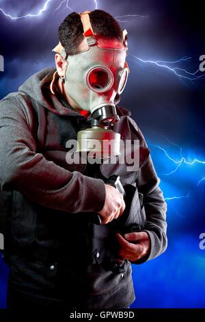 Mann mit Leder Jacke und Angriff Gewehr über Sturm backgr - Stockfoto
