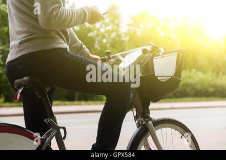 Mann in Casual Kleidung Reiten Fahrrad und konzentriert sich auf Telefon - Stockfoto