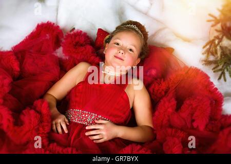 Kleines Winter Prinzessin in eine kostbare Krone im roten Kleid liegt auf Kunstschnee. Begrüßt, Weihnachten und - Stockfoto