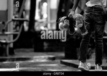 Verlass mich nicht Konzept: Bär Puppe in der Hand von jungen Mädchen - Stockfoto