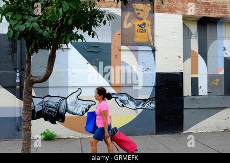 Eine Frau, die zu Fuß durch ein Wandbild entlang Christopher Columbus Drive in Historic Downtown, Jersey City, New - Stockfoto