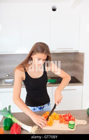 langhaarige junge Frau bereitet eine moderne und stilvolle Küche gesunde Gemüsesalat - Stockfoto
