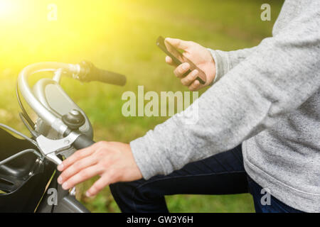 Mann im grauen Pullover auf Fahrrad betrachten Telefon im freien - Stockfoto