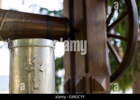 Alter Brunnen mit Trinkwasser und ein Blecheimer mit Kreuz Zeichen in Capriana Kloster in der Republik Moldau - Stockfoto