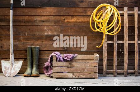 Reihe von Spaten, Gummistiefel und Gartenschlauch von Schuppen - Stockfoto