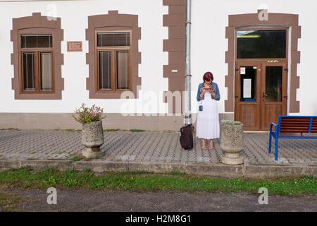 Hübsche Frau Check-Nachricht auf ihr Handy am Bahnhof in Zarnovica, Slowakei - Stockfoto