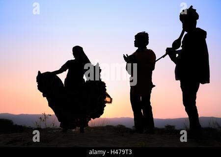 Sonnenuntergang, Silhouette einer Frau, die einen traditionellen Tanz mit zwei Musikern, Pushkar, Rajasthan, Indien - Stockfoto