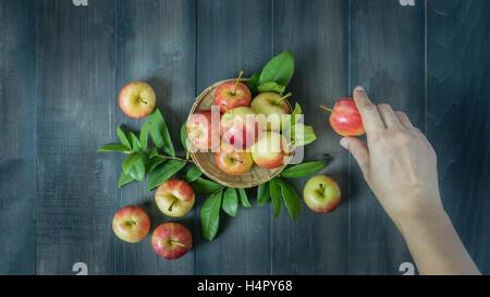 menschliche Hand, die roten und gelben Apfel auf hölzernen Hintergrund, Ansicht von oben - Stockfoto