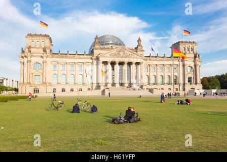 Junges Paar küssen auf einer Wiese vor Reichstagsgebäude in Berlin, Deutschland. - Stockfoto