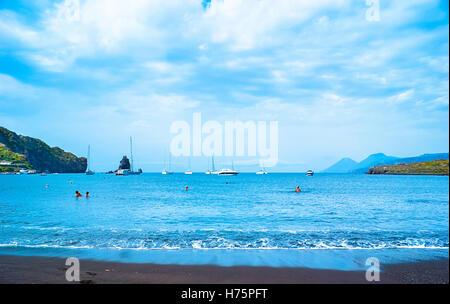 Der schwarze Sandstrand mit Yachten in kleinen Haven und Schwimmen Touristen in Porto di Ponente - Stockfoto