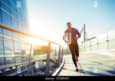 Athlet mit Kopfhörern laufen in der Stadt - Stockfoto