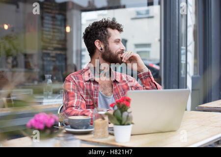 Junge tätowierte Hipster mit Laptop vor café - Stockfoto